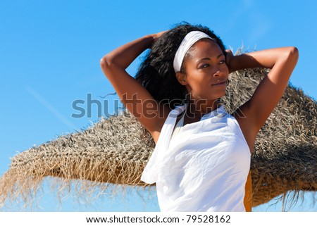 Happy black woman on the beach enjoy the sun