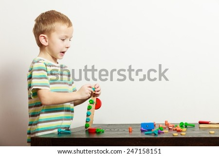 Happy blond boy child kid preschooler playing with colorful building blocks toys interior. At home. Childhood. - stock photo