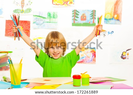 Happy blond boy holding color pencils and lifting hands  - stock photo