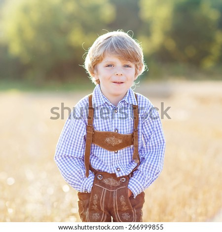 Happy blond boy walking through golden wheat field in summer. - stock photo