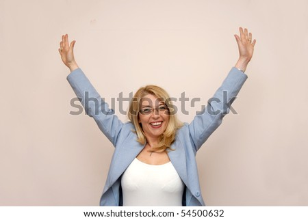 happy blond businesswoman rising up her hands - stock photo
