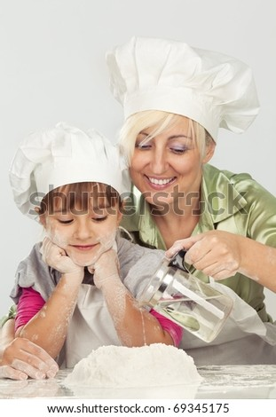 Happy blond caucasian mother and daughter preparing dough and having fun - stock photo