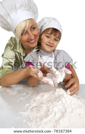 Happy, blond caucasian mother and daughter preparing dough and having fun - stock photo
