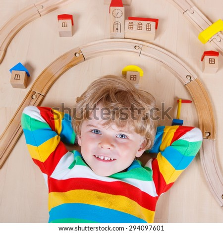 Happy blond child playing wooden trains and railroad indoor. Active kid boy wearing colorful shirt and having fun with building and creating. - stock photo