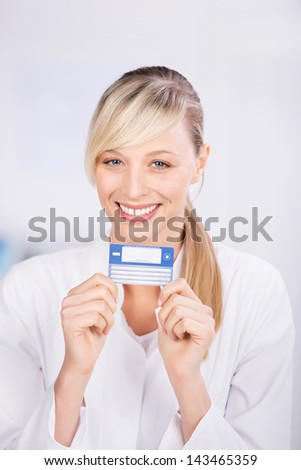 Happy blond doctor showing health card in a close up shot - stock photo