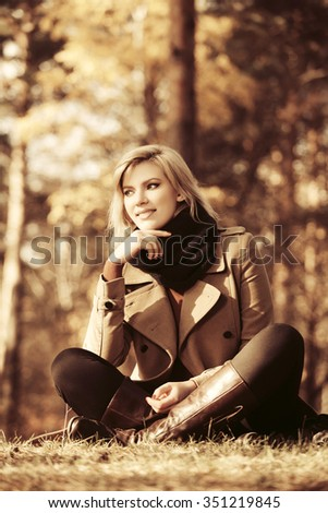 Happy blond fashion woman relaxing in autumn forest