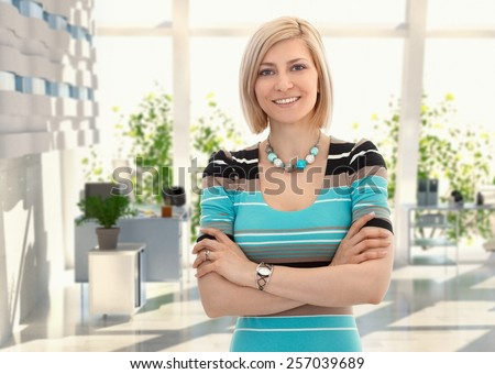 Happy blond female office worker standing arms crossed at office, smiling.