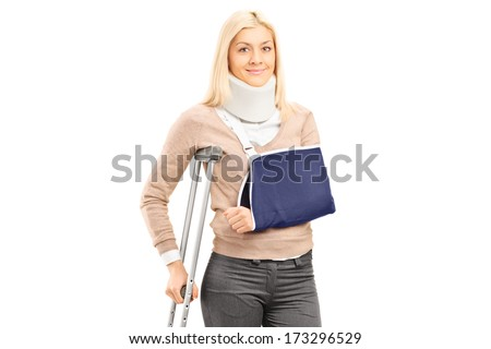 Happy blond female with broken arm holding a crutch posing isolated on white background - stock photo
