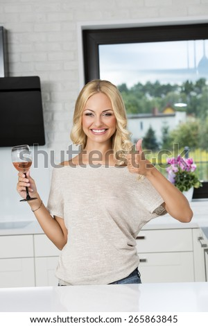 happy blond girl drinking a glass of wine , at home , she is smiling and acting with hand - stock photo