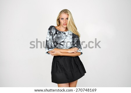 Happy blond girl in a black skirt and blouse - stock photo