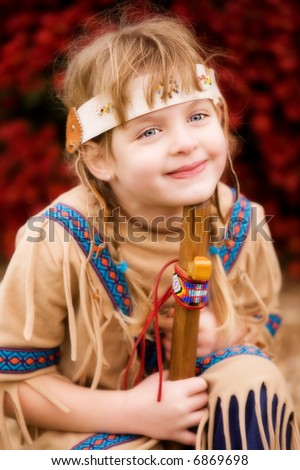 Happy blond girl in native American attire holding a wooden flute.