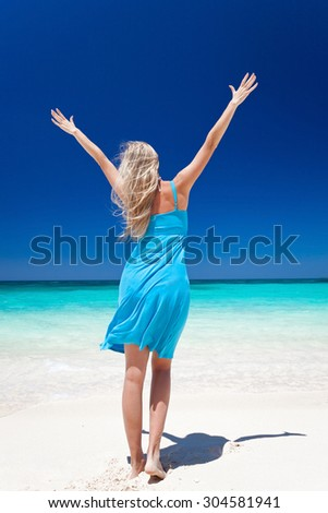 Happy blond girl on beach with outstretched arms, feeling freedom. Back view. Vacation concept - stock photo