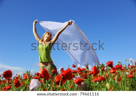 Happy blond girl running in poppy field - stock photo
