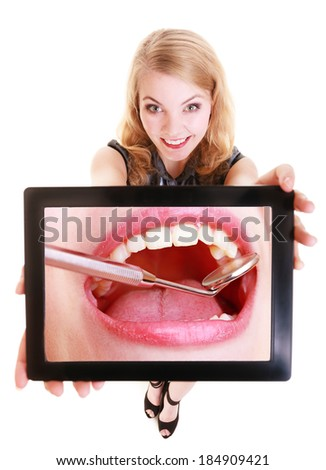 Happy blond girl showing ipad with photo of white female teeth. Modern young woman holding tablet touchpad recommending dental care. Isolated. Technology and health.