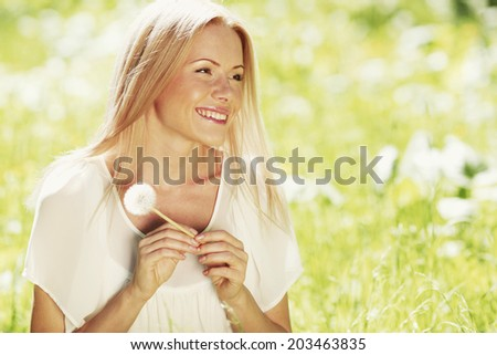 Happy blond Girl with white dandelion in spring park - stock photo