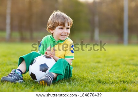 Happy blond little boy of 4 playing soccer with football on football field, outdoors.