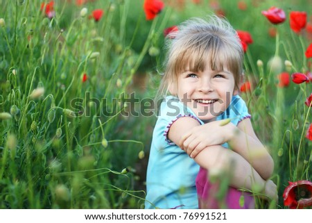 Happy blond little girl on the field of red poppies - stock photo