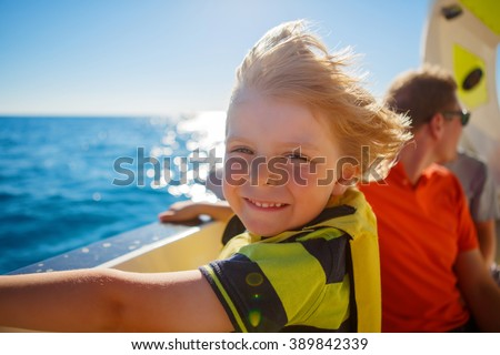 Happy blond little kid boy enjoying sailing boat trip. Family vacations on ocean or sea on sunny day. Child smiling. - stock photo