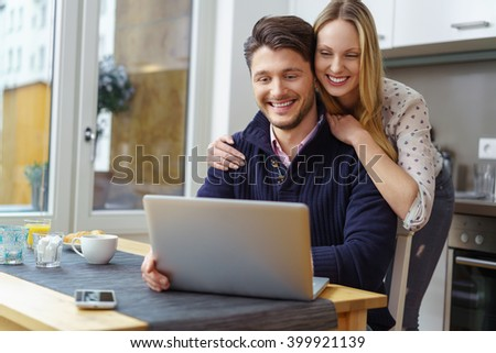 Happy blond woman in dotted blouse leaning on handsome bearded smiling man using laptop at table in kitchen