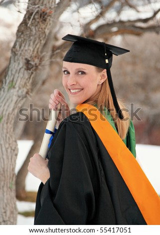 happy blond woman in graduation cap and gown outdoors