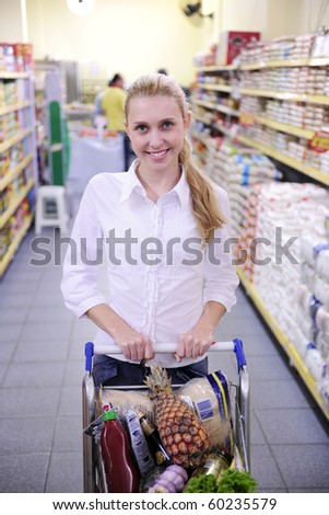 Happy blond woman shopping in the supermarket - stock photo
