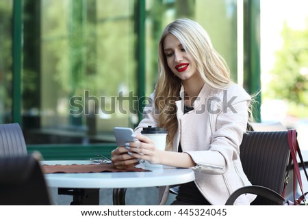 Happy blond woman using the phone sitting in outdoors cafe. Bright makeup, red lips, modern city background
