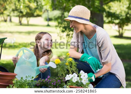 Happy blonde and her daughter gardening on a sunny day - stock photo