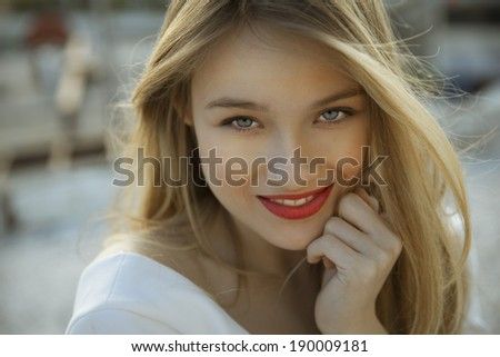 Happy blonde beauty with natural make up and red lipstick. horizontal, outdoors shot. - stock photo