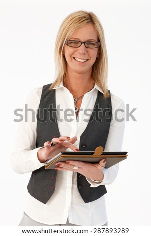 Happy blonde businesswoman smiling, holding tablet, looking at camera.