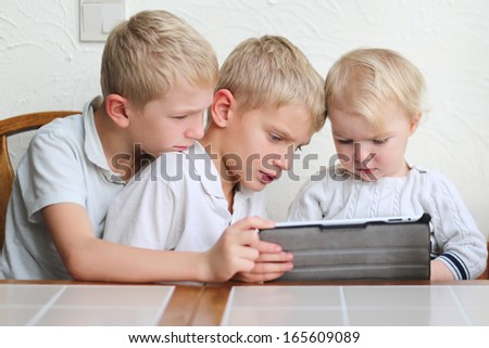 Happy blonde children, two twin brothers with cute toddler sister playing on a tablet at the Kitchen table. - stock photo