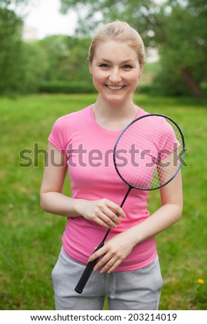 happy blonde girl holding tennis -racket wearing pinck t-shirt outdoor in the park  - stock photo