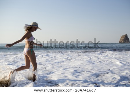 happy blonde girl smiling and run on the beach  wearing swimwear, hat and sunglasses - stock photo