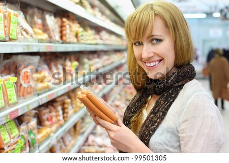 Happy blonde girl wearing white shirt chooses sausage in large store; shallow depth of field - stock photo