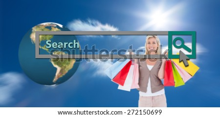 Happy blonde holding shopping bags against sky - stock photo