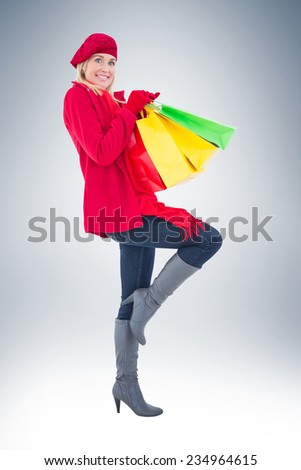 Happy blonde in winter clothes holding shopping bags on vignette background