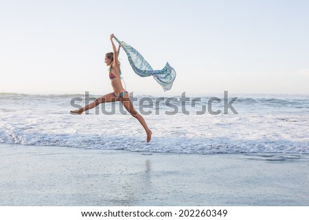 Happy blonde leaping on the beach in bikini with a scarf on a sunny day - stock photo