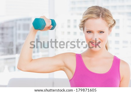 Happy blonde lifting dumbbell and flexing at home in the living room - stock photo