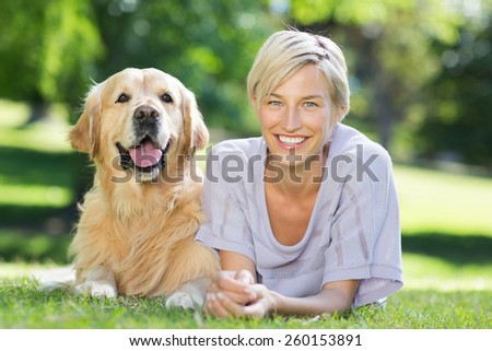 Happy blonde lying with her dog in the park on a sunny day - stock photo