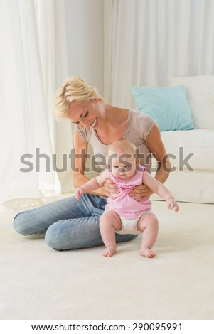 Happy blonde mother playing with her baby girl at home in the living room