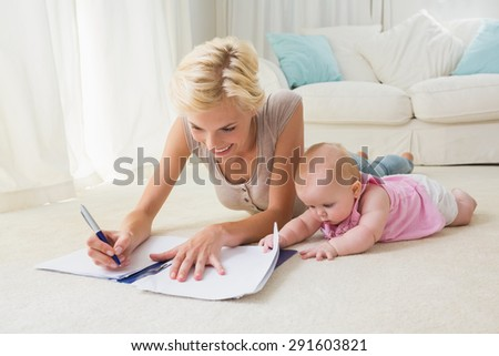 Happy blonde mother with her baby girl writting on a copybook at home in the living room - stock photo