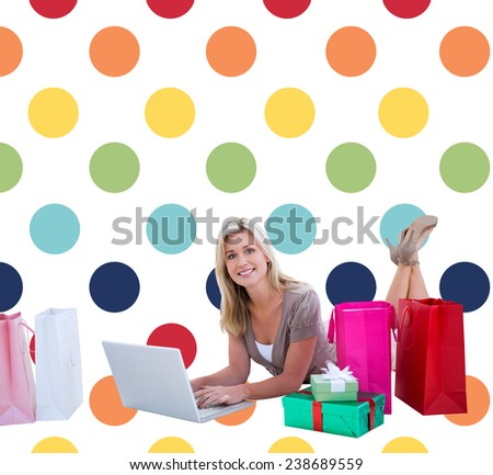 Happy blonde shopping online with laptop against colorful polka dot pattern - stock photo