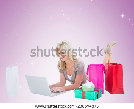 Happy blonde shopping online with laptop on vignette background - stock photo