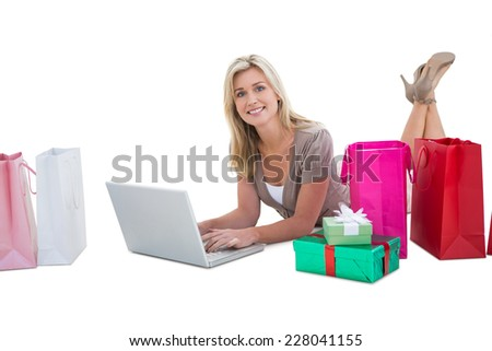 Happy blonde shopping online with laptop on white background - stock photo