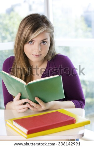Happy blonde teenager female student with books
