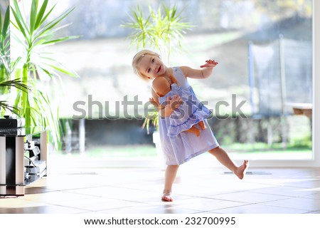 Happy blonde toddler girl having fun dancing with her doll indoors at home or kindergarten in a sunny room with big garden view window - stock photo