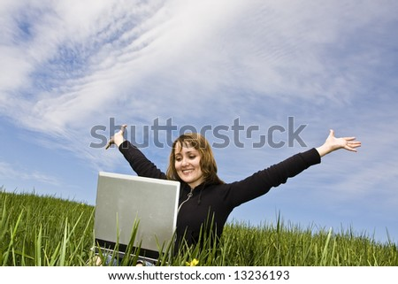 Happy blonde with a laptop in a meadow, arms raised - stock photo