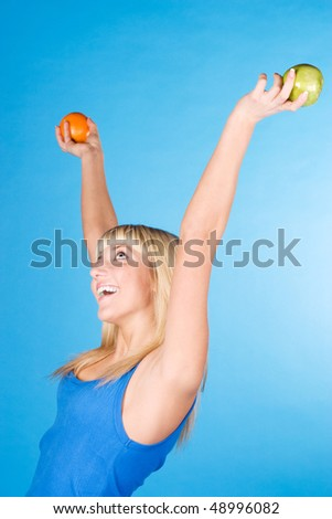 Happy blonde with an apple and an orange in her hands on a blue background