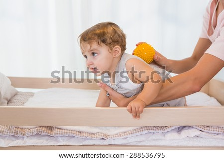 Happy blonde with his son at home in bedroom - stock photo