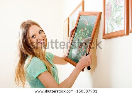 Happy blonde woman hanging  picture with flowers on wall at home