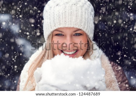 happy blonde woman holding snow and looking at camera